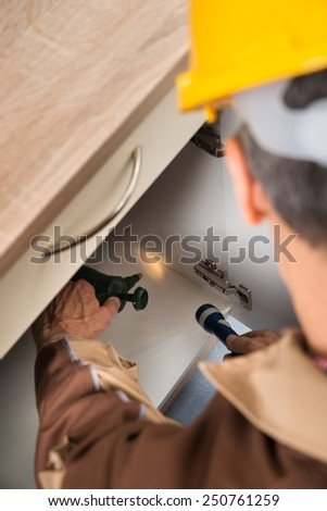 Close-up Of Pest Control Worker Spraying Chemicals With Sprayer In Cabinet - stock photo