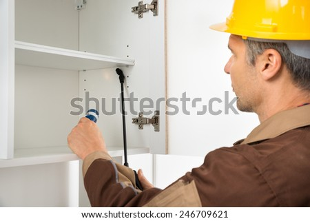 Close-up Of Pest Control Worker Wearing Hardhat Spraying Pesticides On White Shelf - stock photo