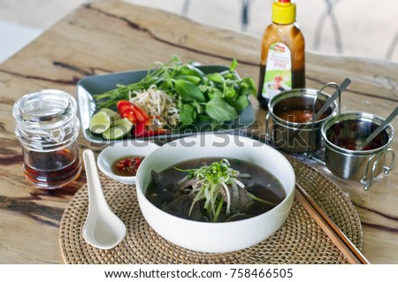 Close up of pho bo, a Vietnamese beef noodle soup with chilli sauce and fresh side salad