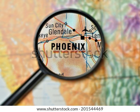 Close up of Phoenix, Arizona under a magnifying glass on a map         - stock photo
