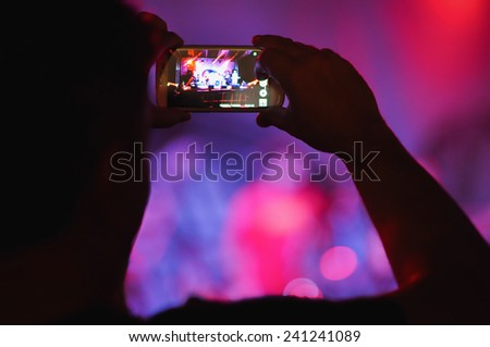 Close up of photographer with smartphone during a concert - stock photo
