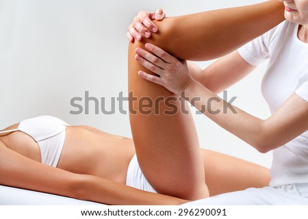 Close up of physiotherapist manipulating female knee. - stock photo