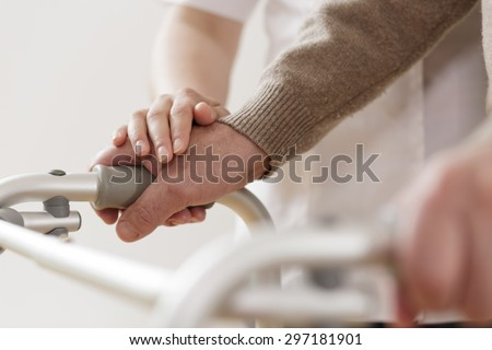 Close-up of physiotherapist supporting disabled senior man - stock photo