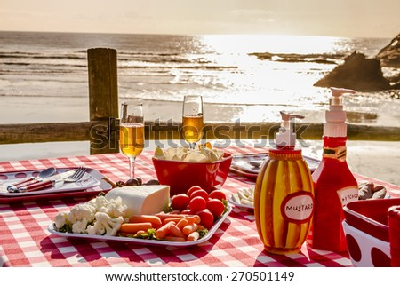 Close up of picnic for 2 at the beach overlooking the ocean with haystack rocks at sunset with table set with food, dishes, wine glasses filled with wine and red checkered table cloth - stock photo