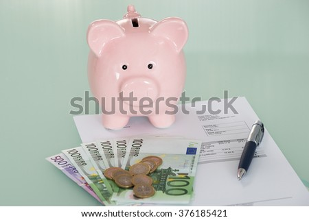 Close-up Of Piggybank And Euro Currency On Desk - stock photo