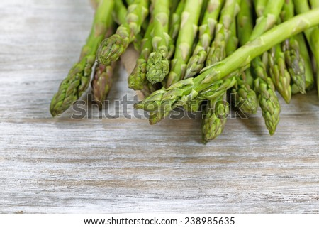 Close up of pile of asparagus; focus on front with shallow depth of field, on rustic white wood  - stock photo
