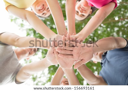 Close-up of pile of friend's hands in the sign on union on the foreground - stock photo