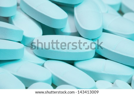 Close-up of pile of white bluish long tablets laying on white tablets