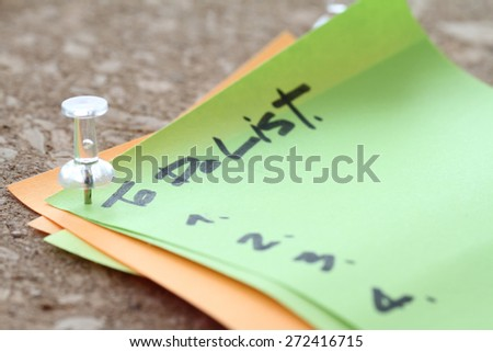 close up of pin and to do list word on sticky note with cork board as concept - stock photo