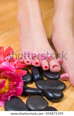 Close up of pink foam spacers between pretty toes with red toenail paint on top of smooth black massage stones and hardwood floor - stock photo