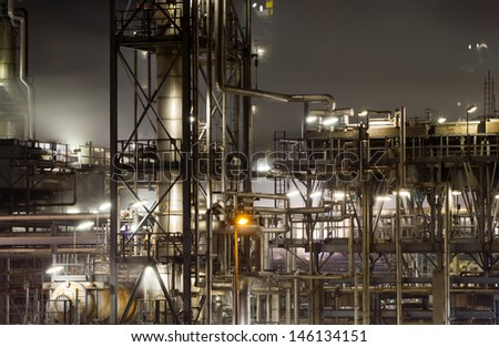 Close-up of pipes and tubes of a large oil-refinery plant at night - stock photo