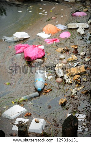 Close up of plastic and polystyrene fast food packaging in a river. - stock photo