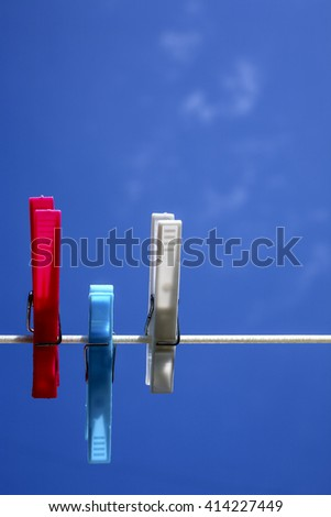 Close-up of plastic clothes pegs with a blue sky background