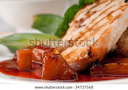 Close up of plate of Mahi Mahi, severd with vegetables, pineapple and soy sauce. - stock photo