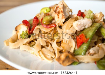 close-up of plate of pasta and chicken with vegetables