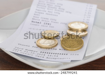 Close-up Of Plate With Bill And Tip On Table - stock photo
