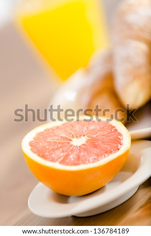Close up of plate with croissants and juice and croissants and juice at the background - stock photo