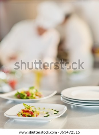 Close-up of plates of colorful cut vegetables arranged in stylish way for a starred restaurant. There are placed on a metallic table in the kitchen. Two chefs are cooking in the blurred background. - stock photo