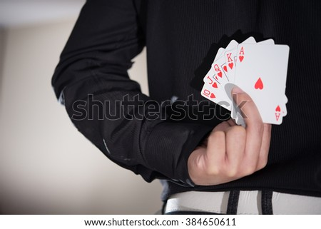 Close-up of poker player holding playing cards behind his back.