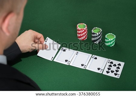 Close-up Of Poker Player Playing Cards On Green Table - stock photo