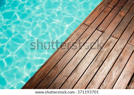 Close up of Pool and wooden floor beside it - stock photo