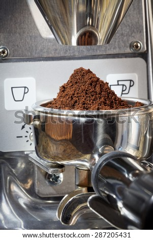 Close-up  of portafilter with focus on freshly ground coffee in the metal cup. Artistic still life scene of the first step in a coffee shop's process to brew an espresso, cappuccino or latte. - stock photo