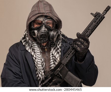 Close up of Post apocalypse man. Doomsday man in gas mask with rifle, trench coat and hood. - stock photo