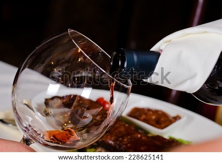 Close Up of Pouring Red Wine into Glass in Restaurant Setting - stock photo