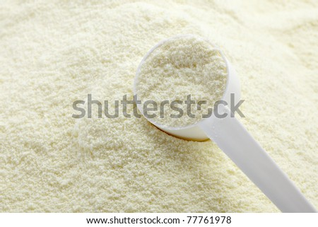 close up of powdered milk and spoon for baby on white background with clipping path