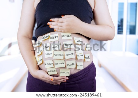 Close up of pregnant belly with baby names on it - stock photo