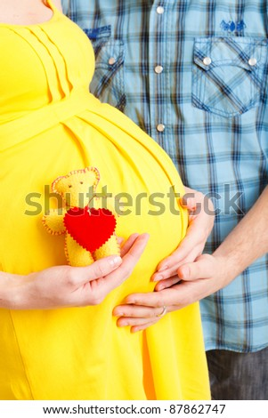 Close-up of pregnant woman and her husband on white background - stock photo