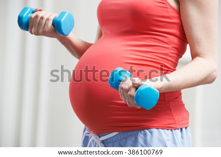 Close Up Of Pregnant Woman Exercising With Weights - stock photo