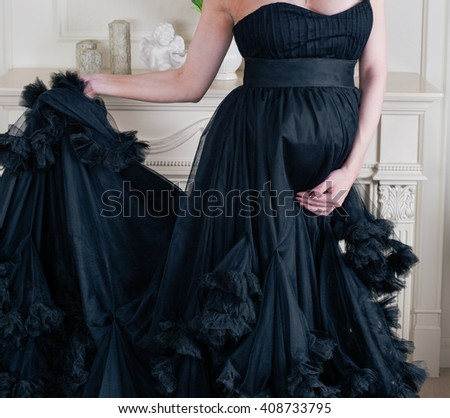 Close-up of pregnant woman keeping her hands on belly. Pregnancy, Abdomen, Human Fertility. Mom Expecting Baby. Maternity concept. Fashion future mother, luxury interior, long rich black dress.  - stock photo