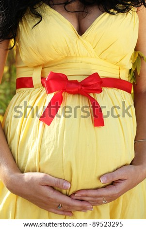 Close-up of pregnant woman's belly with her hand on it - stock photo