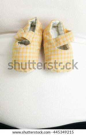 Close up of pregnant woman with green-white baby shoes on tummy - stock photo