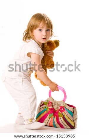 Close-up of pretty baby with toy and bag, isolated over white