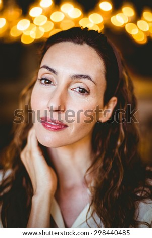 Close up of pretty brunette with hand under her chin looking at camera at the bakery store - stock photo