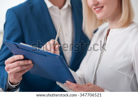 Close up of pretty businesswoman is signing a contract with a estate agent. She is standing and smiling