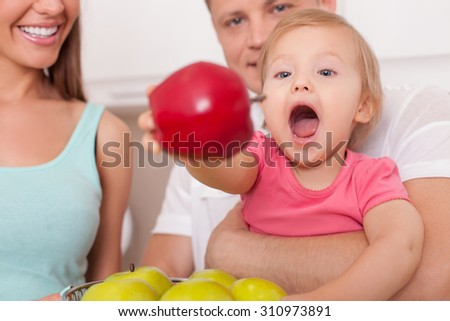 Close-up of pretty child sitting on heads of her father. The girl is taking an apple from the bowl with interest and appetite. Her parents are smiling - stock photo
