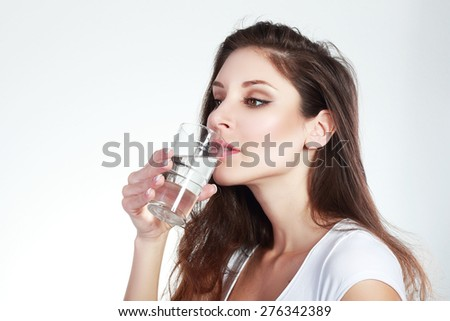Close-up of pretty girl drinking water from glass eyes open - stock photo