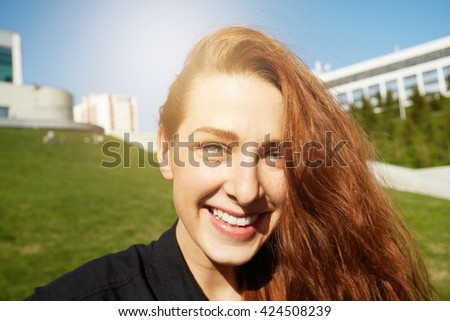 Close up of pretty girl looking and smiling at the camera against green urban background in the public garden. Beautiful young redhead woman waiting for her friends outdoors on sunny summer evening  - stock photo
