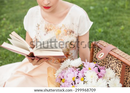 Close up of pretty girl sitting on grass in park. She is reading a book with interest. There is basket of flowers near her - stock photo