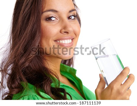 Close-up of pretty girl with glass of water looking at camera - stock photo