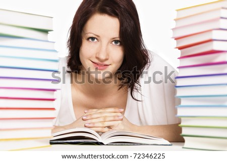 Close up of pretty smiling girl lying on floor between two stacks of colorful books reading and looking straight, isolated on white background. - stock photo
