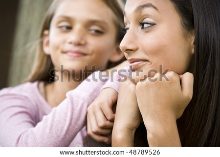 Close-up of pretty teenage girl and younger sister smiling at each other - stock photo