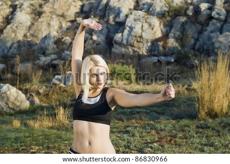 Close up of pretty woman practicing kung fu or tai chi in natural park - stock photo