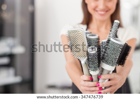 Close up of pretty young hairdresser holding many combs and showing it to the camera. The woman is standing and smiling. Copy space in left side - stock photo