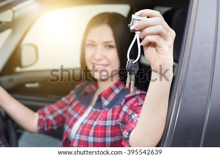 Close up of pretty young woman in car holding and showing keys in hand - stock photo