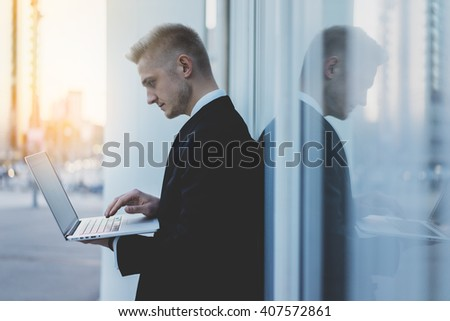 Close-up of professional businessman working on his modern laptop outdoors, male banker wearing suit and using notebook computer near his office outside, flare light - stock photo