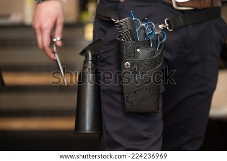 Close-Up Of Professional Equipment Tools Accessories Of Hairdresser - Tools Of A Professional Hairdresser Neatly Stored In A Leather Belt And Pouch Worn Around His Waist In The Hair Salon - stock photo